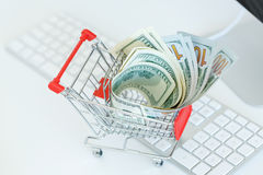 Dollars in the shopping cart on a computer keyboard Stock Photo