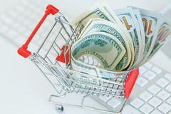 Dollars in the shopping cart - concept of online shopping Royalty Free Stock Photos