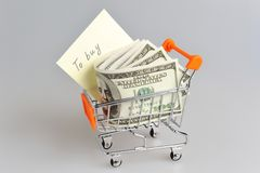 Dollars with shopping list in pushcart on gray Royalty Free Stock Photos