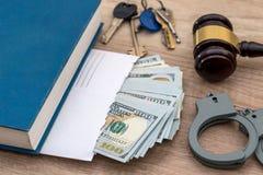 Dollars sous enveloppe, les menottes marteau et le juge de livre Photos stock