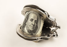 Dollars and steel police handcuffs Royalty Free Stock Images