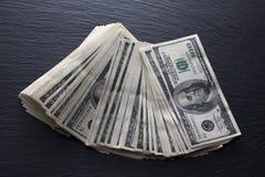 Dollars sur le fond noir de roche Photographie stock libre de droits