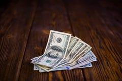 Dollars sur le plancher en bois Image stock
