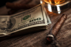 Dollars on the table with glass with brandy and smoking cigarett Royalty Free Stock Photo