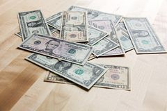 Dollars on the table. Dollars on the oak table top, dollars spread out on the table Royalty Free Stock Image