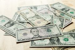 Dollars on the table. Dollars on the oak table top, dollars spread out on the table Stock Images
