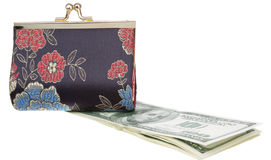 Dollars Theme. Purse on top of a dollars, in a horizontal position , a pack of dollars Royalty Free Stock Photography