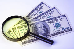 Dollars under a magnifying glass Stock Photos
