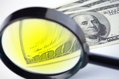 Dollars under a magnifying glass Royalty Free Stock Photos