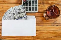 Dollars, une calculatrice et un verre de vin photographie stock
