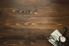 Dollars US et montre de main au-dessus de fond en bois foncé Images stock