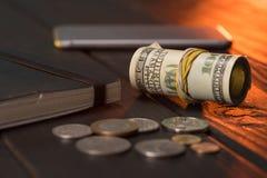 Dollars US et pièces de monnaie avec le carnet et le smartphone Photo libre de droits