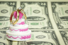 Dollars and wedding cake with rings Stock Photography