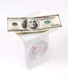 Dollars on the weighing scale Stock Photo