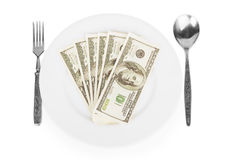 Dollars on a white plate with a fork and spoon Royalty Free Stock Photo