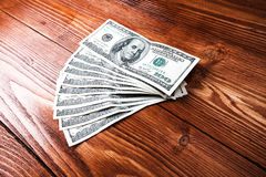 Dollars on wooden table. Fan of one hundred dollars banknotes lying on wooden table Royalty Free Stock Photos