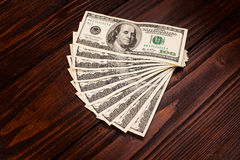 Dollars on wooden table. Fan of one hundred dollars banknotes lying on wooden table Royalty Free Stock Photo