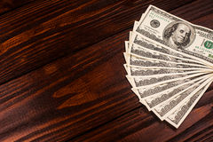 Dollars on wooden table. Fan of one hundred dollars banknotes lying on wooden table Stock Photography