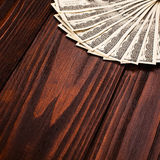 Dollars on wooden table. Fan of one hundred dollars banknotes lying on wooden table Royalty Free Stock Photography