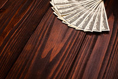 Dollars on wooden table. Fan of one hundred dollars banknotes lying on wooden table Stock Images