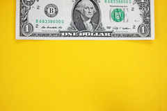 Dollars on yellow backgroudn. Stock Photos