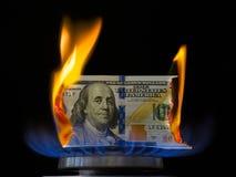 Dollarschein auf Feuer in der Gasbrennerflamme Stockbild