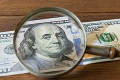 100 Dollarschein unter einer Lupe auf einem Holztisch E Stockfotografie