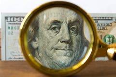 100 Dollarschein unter einer Lupe auf einem Holztisch E Stockfoto