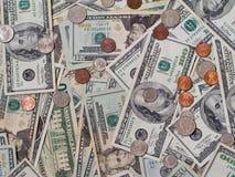 Dollarscheine angehäuft mit Münzen Stockfoto