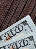 100 Dollarscheine auf einem hölzernen Hintergrund Stockbild