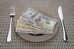 Dollarscheine auf einer Platte mit Gabel und Messer Stockbild