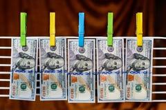 100 Dollarscheine, die an den Wäscheklammern hängen Stockfotografie
