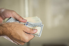 100 Dollarscheine in einer Mann ` s Hand Lizenzfreie Stockbilder
