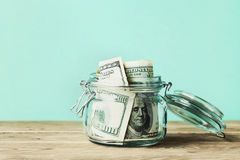 Dollarscheine im Glasgefäß auf Holztisch Hände, die Stapel der Münzen schützen Lizenzfreie Stockfotografie