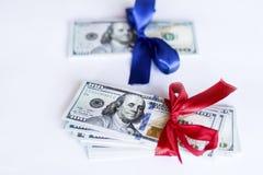 100 Dollarscheine mit rotem und blauem Band auf einem weißen Hintergrund Stockbilder