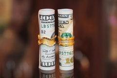 Dollarscheine rollt Geld mit Goldschmuckringen Stockbilder