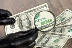 Dollarscheine unter einer Lupe Stockbilder