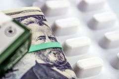 Dollarscheine zusammen mit weißem Pillenpaket, Begriffsbild Lizenzfreies Stockfoto