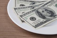 Dollarsedelpengar i den vita plattan Fotografering för Bildbyråer