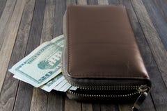 Dollarsedlar, många dollar bildar plånboken på träbackgro royaltyfri foto