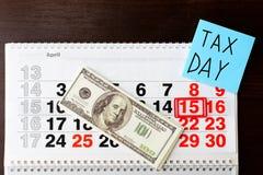 Dollarsgeld, 15 April op kalender, blad van document met Belastingsdag Stock Afbeeldingen