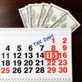 Dollarsgeld, 15 April op kalender en de uitdrukking van de Belastingsdag, houten B Royalty-vrije Stock Foto