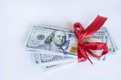 100 dollarsrekeningen met rood lint op een witte achtergrond Stock Foto