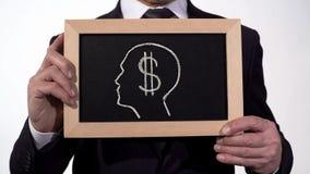 Dollarsymbol-Kopfbild auf Tafel in den Geschäftsmannhänden, Habsucht für Geld stockfoto