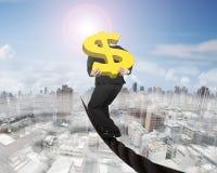 Dollarzeichen des Geschäftsmannes tragendes Gold, dasauf Draht balanciert Lizenzfreies Stockfoto