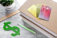 Dollarzeichen und -Kreditkarten für zahlende Bildung auf grauem Studentenschreibtischhintergrund Lizenzfreies Stockbild