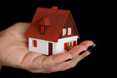 Dollhouse in human hand Stock Image