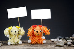 Dolls dog holding a placard Royalty Free Stock Photos