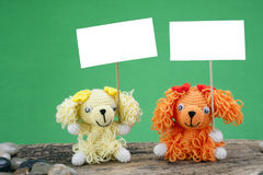 Dolls dog holding a placard. On wood Royalty Free Stock Photos