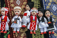 Dolls dressed in traditional Romanian folk costumes-1. Dolls dressed in traditional Romanian folk costumes and set over embroidered materials Royalty Free Stock Photos